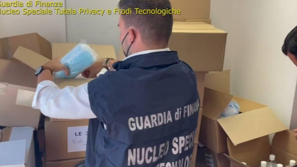 HANDOUT - Italienische Ermittler durchsuchen Pakete mit unter anderem Gesichtsmasken. Foto: Guardia di Finanza/dpa
