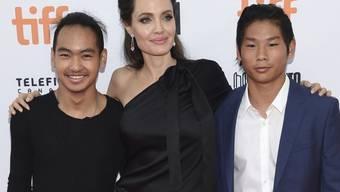 Angelina Jolie (M) mit zwei ihrer sechs Kinder, den Adoptivsöhnen Maddox Jolie-Pitt (r) und Pax Jolie-Pitt. Im laufenden Sorgerechtsstreit zwischen Jolie und Brad Pitt hat ein Gericht der Schauspielerin befohlen, Pitt mehr Aufenthaltszeit mit den Kindern zu gewähren. (Archivbild)