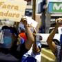 Eine Frau mit Mund-Nasen-Schutz hält bei einer Demonstration in Valencia ein Plakat mit der Aufschrift «Fuera Maduro» (Raus mit Maduro) in die Höhe. Foto: Juan Carlos Hernandez/ZUMA Wire/dpa