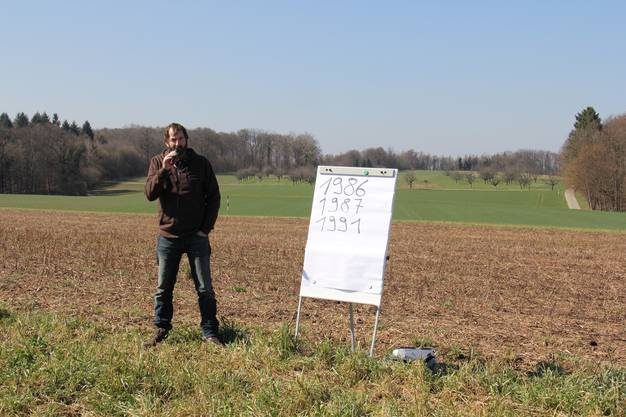 Ruedi Brunner mit einer Tafel, auf der die Jahre notiert sind, in denen schon einmal gebohrt wurde