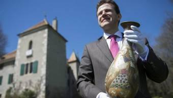 Auktionator Bernard Piguet posiert vor dem Schloss mit einer Vase