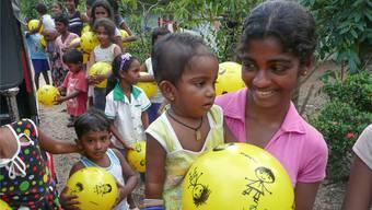 Eine glückliche Mutter mit ihrem Kleinkind und dem neuen Spielball, den sie sich nicht leisten könnte. zvg