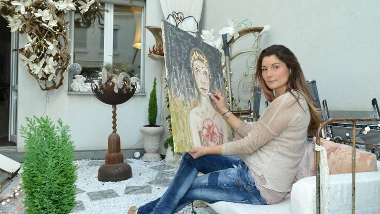Eva Hertwich draussen mit einem ihrer Bilder.