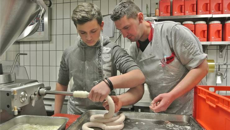 Schüler Mike packt in der Chämi-Metzg beim Wursten mit an – Fleischfachmann Fredy Adamovic unterstützt den 14-Jährigen. ces