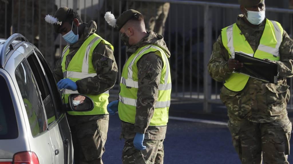 Soldaten führen einen Corona-Test bei einem Autofahrer vor dem Hafen von Dover durch. Foto: Kirsty Wigglesworth/AP/dpa