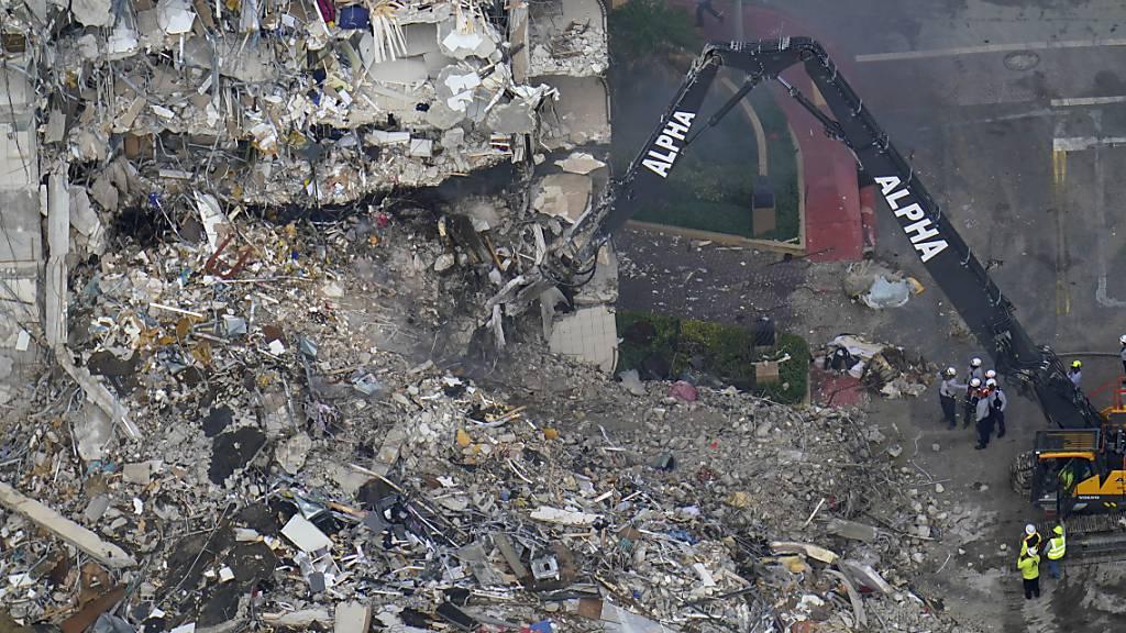 Such- und Rettungskräfte suchen nach Überlebenden in den Trümmern im dem teilweise eingestürzten zwölfstöckigen Gebäude. Foto: Gerald Herbert/AP/dpa