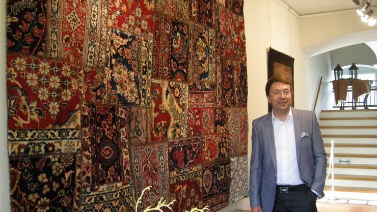 Olivier Ziegler vor einem Patchworkteppich – einem Kunstwerk einer jungen Iranerin. rm