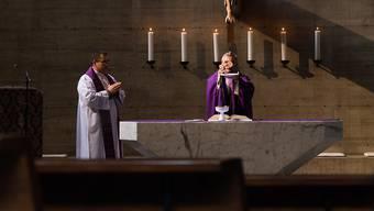 """Tessin wegen des Coronavirus leer gefegt: Der Bischof von Lugano, Valerio Lazzeri (rechts), zelebriert in der leeren Kirche """"Cristo Risorto"""" die Messe."""