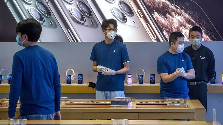 Angestellte in einem Apple-Store in Peking tragen wegen des Coronavirus Atemmasken. (Archiv)