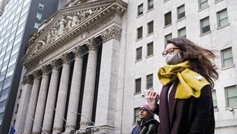 Eine Frau trägt vor der Börse in New York eine Gesichtsmaske.