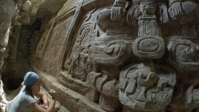 Eine Archäologin reinigt einen Teil des Reliefs von Holmul