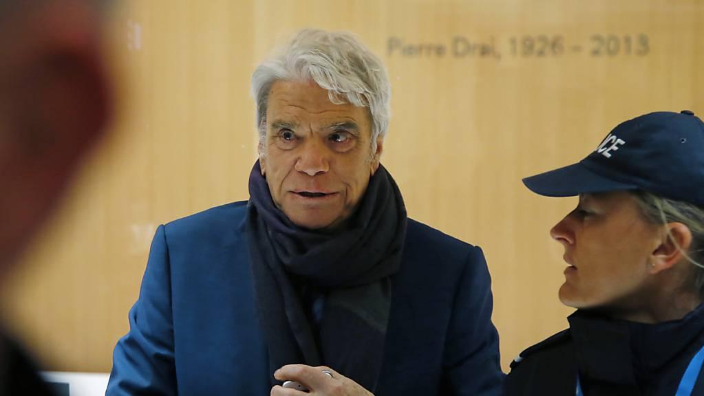 Bernard Tapie (l), französischen Manager, Ex-Minister, Schauspieler und Fussballmanager, kommt in Begleitung einer Polizistin an einem Pariser Gericht an. Ein brutaler Einbruch bei Tapie sorgt für Entsetzen in Frankreich.
