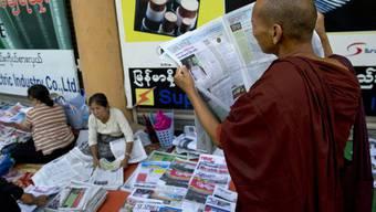 Strassenszene aus Burma: Ein buddhistischer Mönch liest am Montag in einer der vier neuen Tageszeitungen