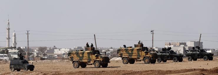 Türkische Soldaten auf bewaffneten Fahrzeugen.