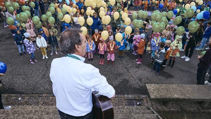 Lied unter regenverhangenem Himmel: Die Kinder stehen auf dem Pausenplatz des Schulhaus Büel.