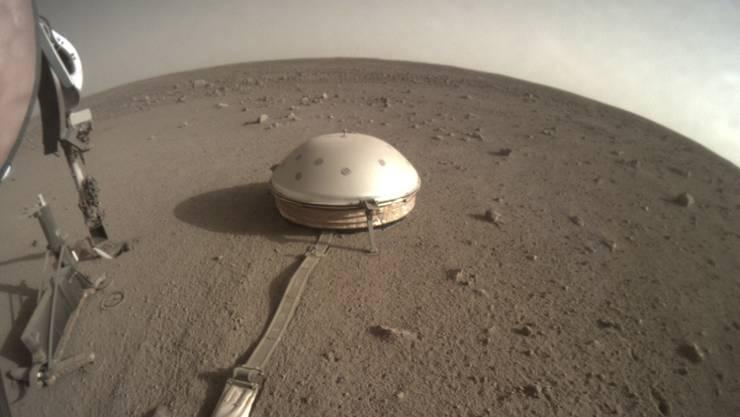 """Das Seismometer """"SEIS"""" unter seiner Schutzhaube auf der Marsoberfläche. Seit seiner Inbetriebnahme hat es 450 Marsbeben aufgezeichnet."""