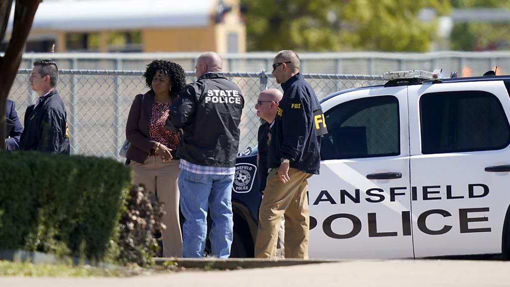 Polizeibeamte versammeln sich auf dem Parkplatz der timberview High School. Foto: Lm Otero/AP/dpa