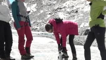 Mit dem Eisbohrer entnehmen die Schülerinnen einen Eisbohrkern aus dem Gletscher. An Eisbohrkernen und den eingeschlossenen Gasbläschen können Forschende die Klimavergangenheit rekonstruieren.
