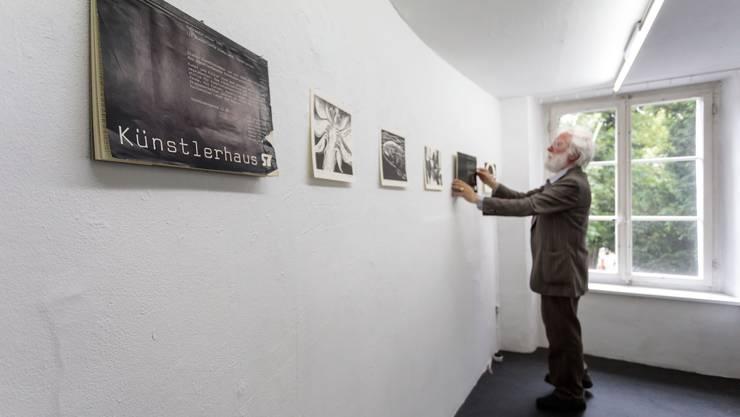 Fritz Breiter, selber Künstler, hängt sorgfältig die Bilder der Jahreskalender im Künstlerhaus auf.