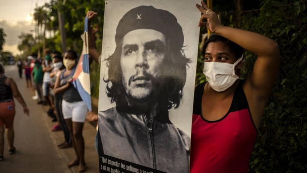Frau in Havanna wartet während der Corona-Krise auf die Mediziner-Brigade des Henry Reeve Contingent und hält dazu das ikonische Foto «Guerillero Heroico» von Che Guevara hoch, das offenbar für jeden Anlass passt. Die Wohnung, in der Che geboren wurde, wird Fans zum Verkauf angeboten. (Archivbild)