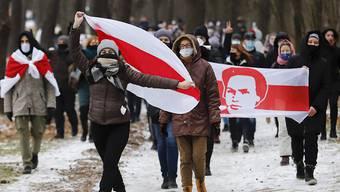 dpatopbilder - Demonstranten mit Mund-Nasen-Schutz tragen bei einer Kundgebung, auf der sie den Rücktritt von Machthaber Lukaschenko fordern, Fahnen in den Farben der früheren belarussischen Nationalflagge. Foto: ---/AP/dpa