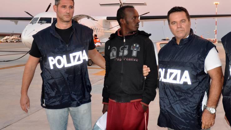 Dieser Mann (Mitte) wurde von der italienischen Polizei festgenommen, weil er im Verdacht steht, Flüchtlinge gefoltert und vergewaltigt zu haben