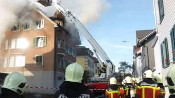 Die Feuerwehr beim Löschen des brennenden Mehrfamilienhauses am Freitagmorgen in Uzwil SG. Ein Feuerwehrmann wurde dabei verletzt (Bild: Kantonspolizei St. Gallen)