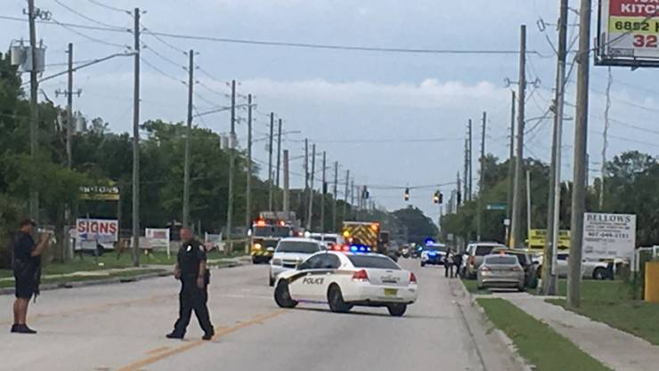Nach einem bewaffneten Angriff auf eine Firma sichert die Polizei die Umgebung in einem Industriegebiet von Orlando.