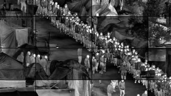 """In seinem 16-Kanal-Video """"Grid (Moria)"""" dokumentiert und überwacht der kanadische Künstler Richard Mosse das Leben in einem überfüllten Flüchtlingslager auf Lesbos."""