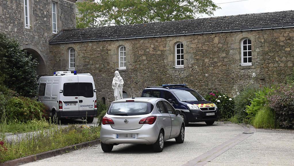 Fahrzeuge der Gendarmerie parken am Ort, an dem in ein 60-jähriger katholischer Priester ermordet wurde. In der Nähe der westfranzösischen Stadt Nantes ist Berichten des Senders Franceinfo zufolge ein katholischer Priester in der kleinen Gemeinde Saint-Laurent-sur-Sèvre getötet aufgefunden worden. Foto: Sebastien Salom-Gomis/AFP/dpa