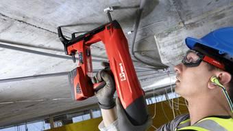 Ein Bauarbeiter mit einen Akkuschrauber von Hilti. Der Konzern ist einer der Eckpfeiler der Liechtensteiner Industrie und Wirtschaft.