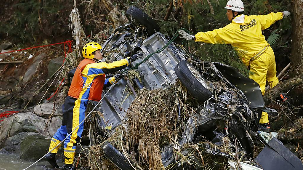 Rettungskräfte bergen nach dem Taifun «Hagibis» ein Autowrack aus einem Fluss bei Koriyama in der Nähe von Fukushima.