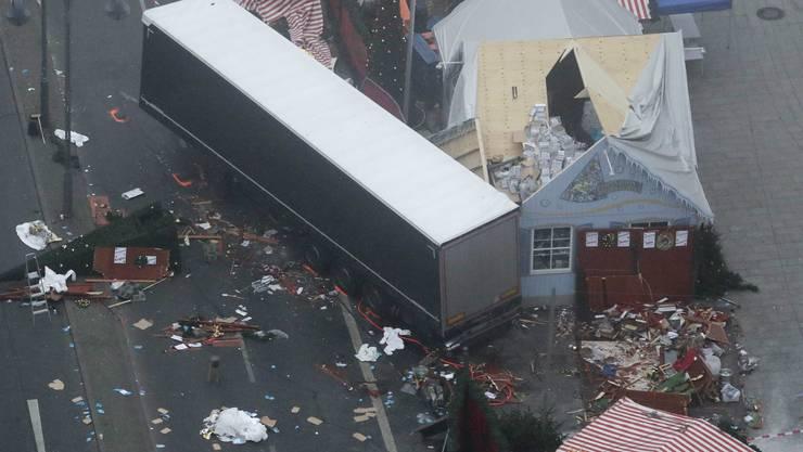 Der Morgen danach: Der Lkw-Anhänger neben zerstörten Weihnachtsstände und -hütten.