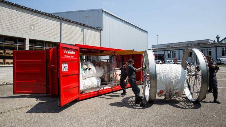 Auf grossen Rädern rollen Feuerwehrleute die Schlauchelemente zum Einsatzort. Der Container ist mobil.