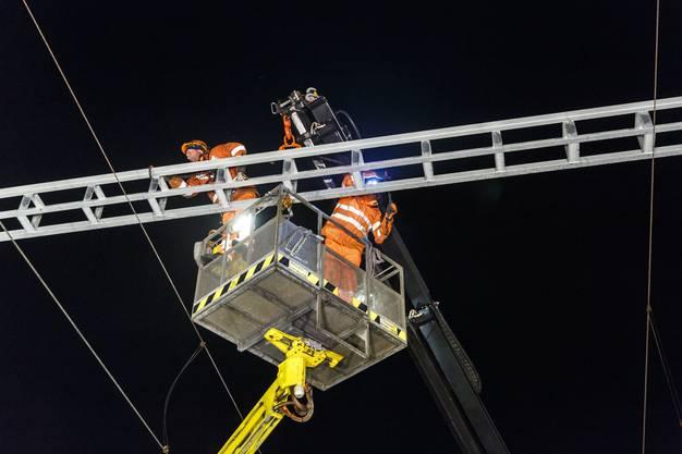 Der Querträger wird von den Arbeitern der Oensingen-Balsthal-Bahn (OeBB) am Mast verschraubt.