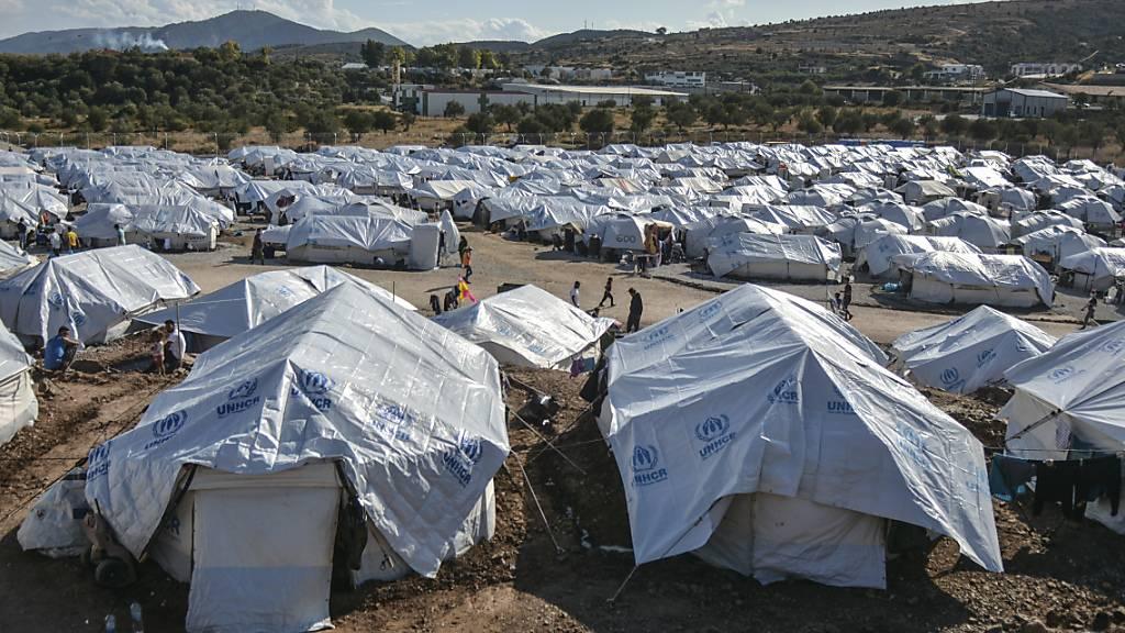 ARCHIV - Migranten gehen nach starken Regenfällen durch das Flüchtlingslager «Kara Tepe». Foto: Panagiotis Balaskas/AP/dpa