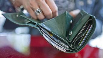 Eine Frau hält ihr geöffnetes Portemonnaie in der Hand (Symbolbild)