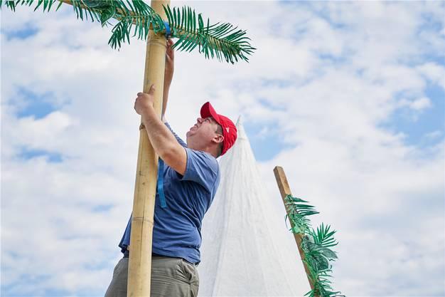 Dieser Helfer stellt in luftiger Höhe tropische Dekorationen für eine Bar auf.