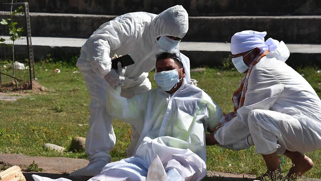 Kein Trost und kaum Hoffnung in Indien: Ein Angehöriger einer Frau, die an den Folgen einer Corona-Infektion verstorben ist, bricht während der Einäscherung zusammen. Foto: Nazim Ali Khan/ZUMA Wire/dpa