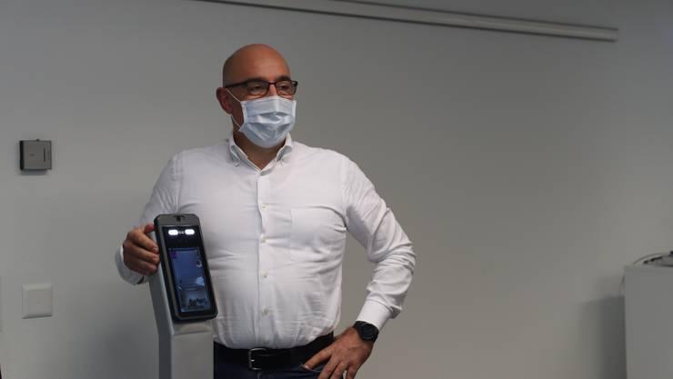 Dino Prosdocimi, Verkaufsleiter der Schlieremer Firma Ruf Avatech mit dem neuen Gerät zur Temperaturmessung und Erkennung ob die Person eine Maske auf hat.