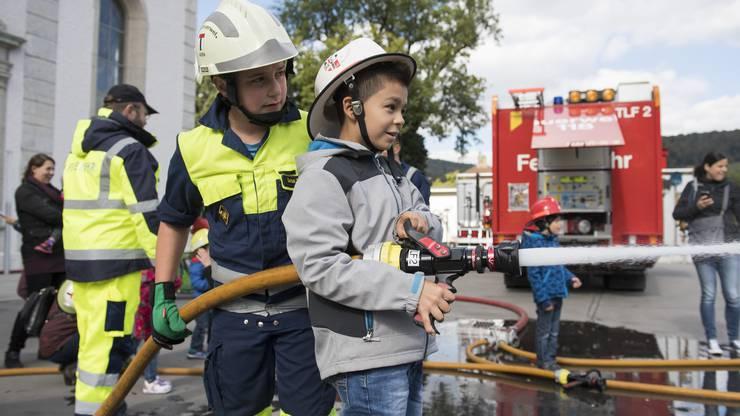 Die Jugendfeuerwehr Baden lässt die Kindern Wasser spritzen und Harrassen klettern während Kids City, Bahnhofplatz Baden, 5. Oktober 2016.