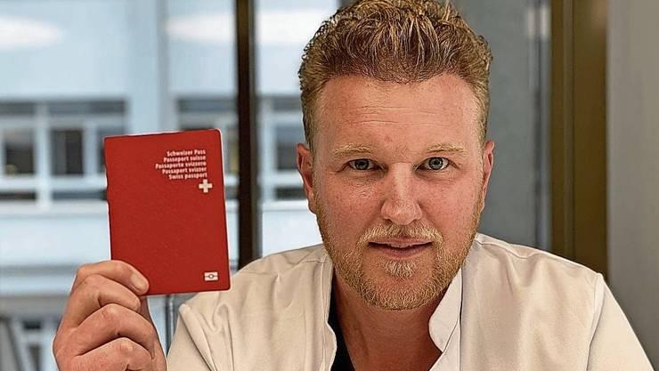 Felix Bertram zeigt stolz seinen Schweizer Pass.