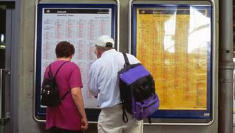 Reisende studieren den Fahrplan im Bahnhof Olten.