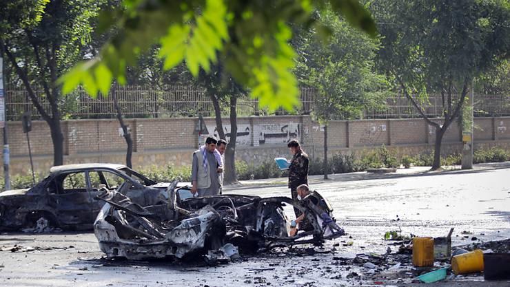 Sicherheitskräfte untersuchen den Tatort nach einem Bombenanschlag vor der Universität in Kabul - mindestens acht Menschen wurden getötet, mindestens 33 weitere erlitten Verletzungen.