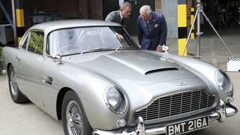 """Schauspieler Daniel Craig und Prinz Charles freuen sich am Aston Martin """"Bond-Auto"""" - weniger Freude haben derzeit allerdings die Aktionäre des Autoherstellers an ihren Papieren. (Archivbild)"""
