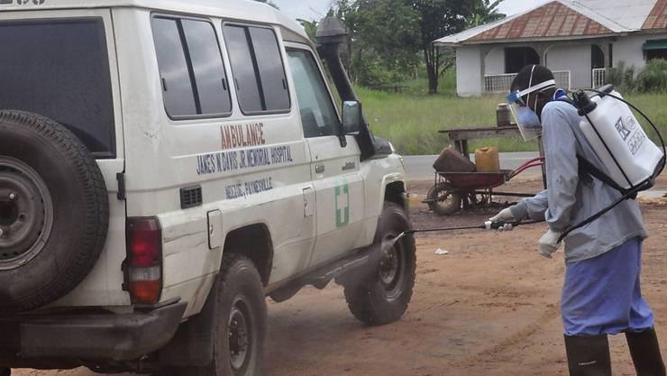 Ein Ambulanz-Fahrzeug wird nach einem Ebola-Einsatz in Monrovia, Liberia, desinfiziert. Liberia, Sierra Leone und Guinea ersuchen um Milliardenhilfen, um ihre Gesundheitssysteme aufzurüsten (Archivbild).