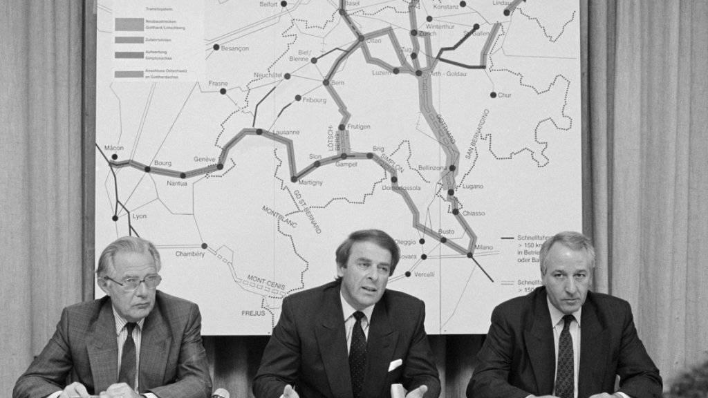 Bundesrat Adolf Ogi, Mitte, und Fritz Bürki, Direktor Bundesamt für Verkehr, links, präsentieren am 28. Mai 1990 in Bern die Botschaft über den Bau der Schweizerischen Eisenbahn-Alpentransversale NEAT. Am 27. September 1992 nahm das Stimmvolk den Beschluss mit 63,6 Prozent Ja-Stimmen an.