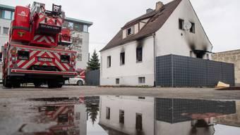 Ein Feuerwehrwagen steht neben einem Haus mit Brandspuren. Bei dem Brand in dem Nürnberger Wohnhaus sind vier Kinder und eine Frau ums Leben gekommen.