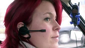 Eine Frau benützt eine Freisprecheinrichtung im Auto (Symbolbild)