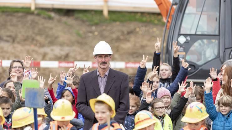 Gemeindeammann Max Härri umgeben von Schulkindern beim Spatenstich.